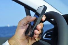 Man genom att använda en smartphone, medan köra en bil Arkivbild