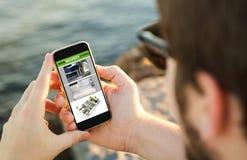 Man genom att använda hans mobiltelefon på kusten till att övervaka webcams Royaltyfri Bild