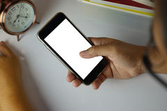 Man genom att använda hans mobiltelefon på tabellen med den vita skärmen royaltyfria bilder