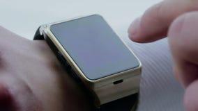 Man genom att använda hans smartwatch app på dagligt ljus stock video