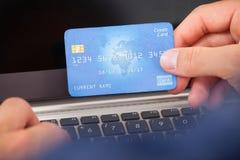 Man genom att använda kreditkorten och bärbara datorn för att shoppa direktanslutet Arkivbilder