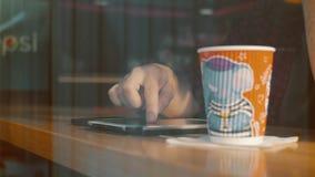 Man genom att använda minnestavlan och dricka kaffe i kaféfönster stock video