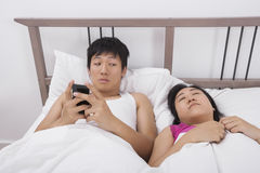 Man genom att använda mobiltelefonen, medan se kvinnan som sover i säng Fotografering för Bildbyråer