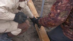 Man genom att använda skruvmejselskruvningsbulten till träbrädet för att fixa metallarbete stock video