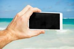Man genom att använda smartphonen för att ta fotoet på en strand Arkivbild