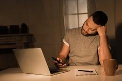 Man genom att använda smartphonen i fundersamt poserar, medan sitta nära bärbara datorn hemma Royaltyfri Foto