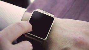 Man genom att använda smartwatch app med hans finger på den wood tabellen arkivfilmer