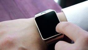 Man genom att använda smartwatch app med hans finger på den wood tabellen lager videofilmer