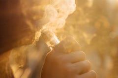 Man genom att använda vape eller den elektroniska cigaretten mot bakgrunden av Arkivbilder