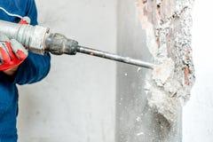 Man genom att använda en tryckluftsborr för att borra in i väggen Royaltyfri Foto