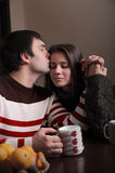 Man gently kisses the girl at breakfast. Sitting at the table and curled hands Stock Photo