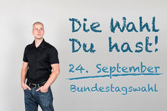 Man with german appeal to go vote at german federal election 201. Young man next to german appeal die wahl du hast meaning it`s your choice for german federal Stock Images