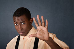 Man Gestures Stay Back. Young handsome Black male gestures with palm to stay away Stock Image