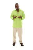 Man Gesturing. Casual young African American man standing in a bright green shirt with hands gesturing inward Stock Images