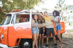 Man gesturing away while standing with friends by camper van Stock Images