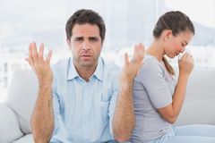 Man gesturing at camera with his crying partner on the couch Royalty Free Stock Image