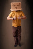 man gesturing with a cardboard box on his head with evil f Stock Image