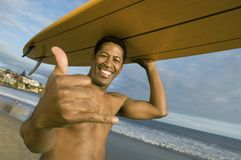 Man Gesturing While Carrying Surfboard On Head Royalty Free Stock Photo
