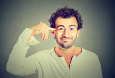 Man gesturing with finger against temple asking are you crazy? Stock Image