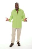 Man Gesturing With Hands Apart. Casual young African American man standing in a bright green shirt with a welcoming hands apart gesture Royalty Free Stock Image