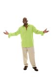 Man Gesturing With Hands Apart. Casual young African American man standing in a bright green shirt with a welcoming hands apart gesture Royalty Free Stock Images