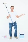 Man gesturing while holding paint roller. Full length portrait of man gesturing while holding paint roller on white background Royalty Free Stock Image