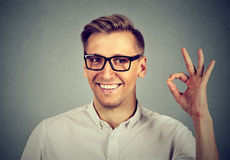 Man gesturing OK sign isolated on gray background. Man gesturing OK sign isolated on gray wall background Stock Photos