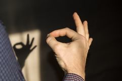 Man gesturing OK sign on the wall the shadow of a hand Royalty Free Stock Photography