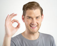 Man gesturing OK sign. Young man gesturing OK sign on light background Stock Image