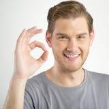 Man gesturing OK sign. Young man gesturing OK sign on light background Stock Photos