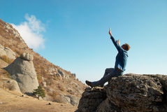 Man gesturing with raised arms. With rocks landscape background Stock Images