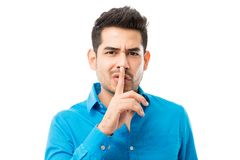 Man Gesturing Silence With Finger On His Lips. Handsome young man gesturing silence with finger on his lips over white background royalty free stock image