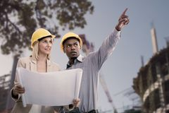 Composite image of man gesturing while standing with female architect. Man gesturing while standing with female architect against low angle view of construction Royalty Free Stock Image