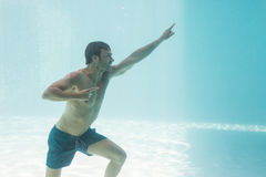Man gesturing while standing underwater Royalty Free Stock Images