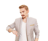 Man gesturing thumb down sign isolated at white. Young stylish guy with mustache in suit showing negative emotion. Sarcastic male portrait symbolising loss and Royalty Free Stock Images
