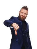 Man gesturing thumb down sign isolated at white. Young stylish hipster with beard in blue suit showing negative emotion. Sarcastic male portrait symbolising Stock Photography
