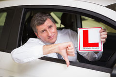 Man gesturing thumbs down holding a learner driver sign Stock Photos