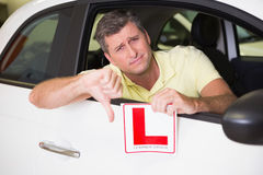 Man gesturing thumbs down holding a learner driver sign Royalty Free Stock Images