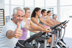 Man gesturing thumbs up with class at spinning class Stock Photo