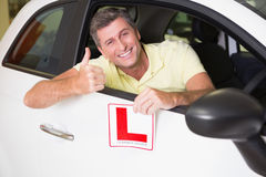 Man gesturing thumbs up holding a learner driver sign. At new car showroom stock photos