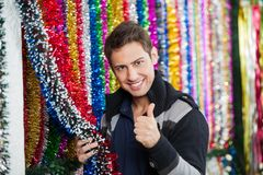 Man Gesturing Thumbs Up While Holding Tinsels At Royalty Free Stock Photography