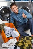 Man Gesturing Thumbs Up At Laundry Stock Photo