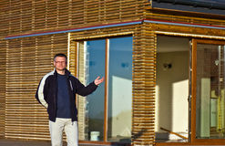 Man gesturing towards new home. Man gesturing towards newly constructed environmentally friendly wooden home Royalty Free Stock Photography