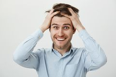 Man gets crazy with pressure at work. Portrait of weird funny european male in casual shirt, holding hands on hair and. Smiling, being excited or thrilled with Stock Image