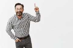 Man gets excited of everything. Portrait of impressed and amused good-looking businessman in striped shirt and pants. Bending towards camera while discussing stock image