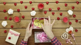 Man gets handmade paper valentine heart as valentine day present, top view. Top view shot of male hands unboxing gift box with handmade paper valentine heart stock footage