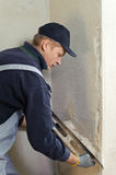 Man gets manually gypsum plaster Royalty Free Stock Image
