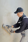 Man gets manually gypsum plaster Royalty Free Stock Photo