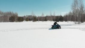 A man gets off the quad in the middle of a snow-covered field. A man gets off the quad in the middle of a snow-covered field - Shot from drone stock footage