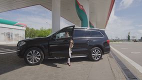 Man Gets Off Vehicle Takes Daughter Leaves to Refuel Tank. KAZAN, TATARSTAN/RUSSIA - AUGUST 25 2017: Man gets out of vehicle with daughter and leaves jeep to stock footage